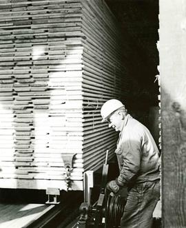 Workman with stack of lumber