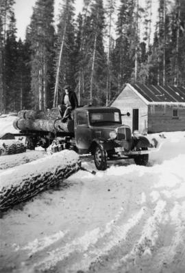 Man atop a log truck in winter at Peden Hill sawmill