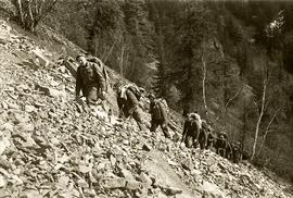 [Soldiers hiking single file on rocky slope]