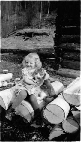 Young Mabel Scholander seated on a wood pile holding a cat