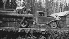 Logging truck on corduroy log road with passengers