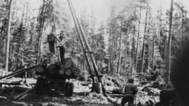 Loggers using a gin pole, winch and jammer to load logging truck