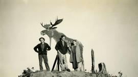 Jack Lee, Gordon Wyness, and Lavender Monckton in front of wooden moose in Prince George