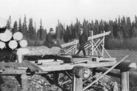 Men on log platform near sawmill