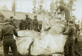[Soldiers transferring water from military truck water bag to a large water bag on the ground]