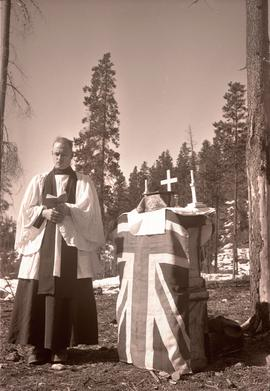 [Military chaplain reading by a makeshift altar with the Union Jack]