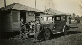 Jack Lee, Gordon Wyness, and Lavender Monckton sitting on car in front of Prince George cabin