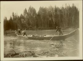 Three unidentified men poling a canoe up Nass River, BC