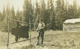 A man holding a rifle standing next to a stretched bear skin