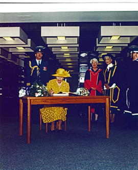 Queen Elizabeth II signs guest book while Chancellor Iona Campagnolo, University Librarian Pat Appavoo, and Geoffrey R. Weller look on