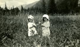 Young Marion and Joyce Collison in meadow at Kincolith, BC