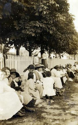 Group of women and children sitting in the shade