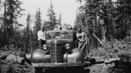 Men on 'Maple Leaf' Chevrolet truck running board while hauling raw logs