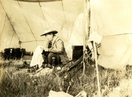 Harry Snyder sitting under a tent cleaning his rifle