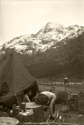 [Two soldiers by tent with morning coffee, trying on snowshoes]