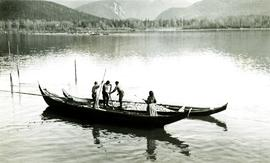 Unidentified men and woman standing in canoes: Oolichan fishing on Nass River, BC