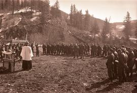 [Military chaplain reading by a makeshift altar to a large group of soldiers]