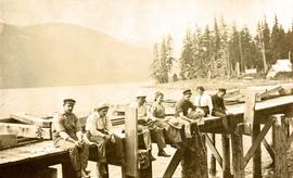 Collison family sitting on dock in Portland Canal, BC
