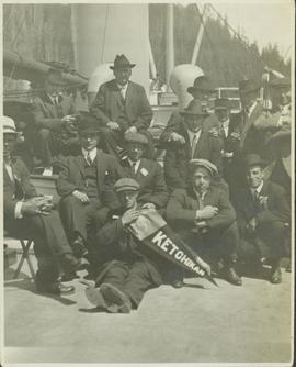 "Group photo of men in suits aboard a steam ship holding up a ""Ketchikan"" pennant"