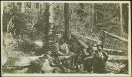 Crew Sitting on Felled Logs in Forest