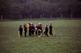 Young children with hula hoops on a field in East Germany