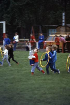 children running with a toy bear and hula hoops in East Germany