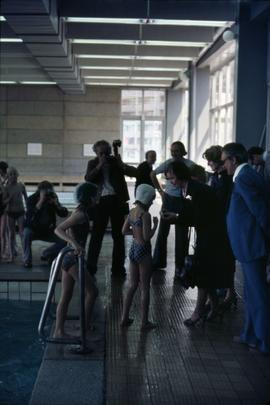 Iona Campagnolo interacting with a young female swimmer while standing in a group of unknown peop...