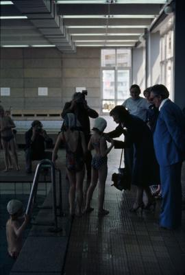 Iona Campagnolo interacting with a young female swimmer at an aquatic centre in East Germany