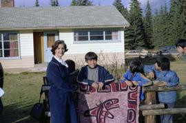 Iona Campagnolo standing with children by a blanket depicting First Nations whale art