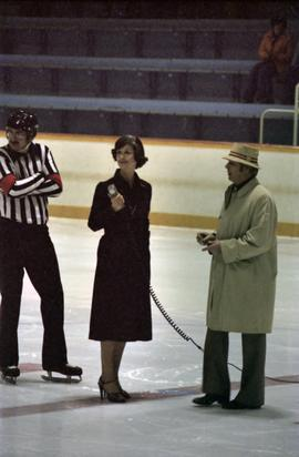 Iona Campagnolo speaking into microphone on Kitimat ice rink by hockey referee and man