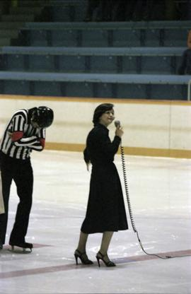 Iona Campagnolo speaking into microphone on Kitimat ice rink with hockey referee nearby