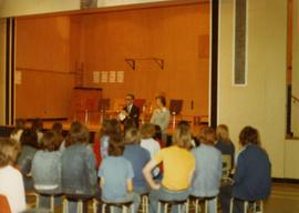 Iona Campagnolo standing in front of students in Babine Elementary-Secondary School auditorium in...