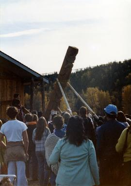 Kispiox community members watching a totem pole being raised