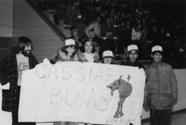 "Iona Campagnolo holds a ""Cassiar Bums"" sign with Ken Maddson, Carol Fugere, Ghislaine Berube, Anil Kaul and Atul Kaul at a sporting event"