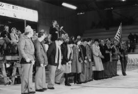 Jan Kapicky with a line of unidentified adults in front of a stage in an arena