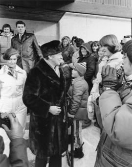 Iona Campagnolo and Pierre Trudeau talk with a crowd at a children's speed skating event