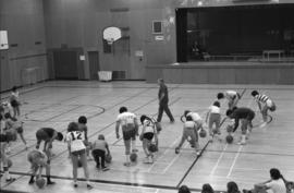 Mount Elizabeth Secondary School students dribble basketballs in a physical education class