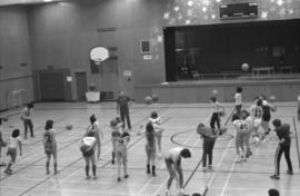 Mount Elizabeth Secondary School students toss basketballs in a physical education class