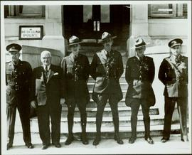 Group photo of five men in uniform and one in a suit standing outside the British Columbia Police building