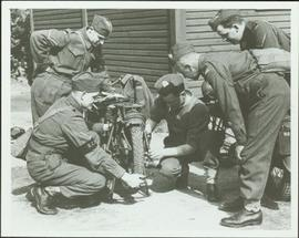 Working on a motorcycle at the No. 1 Canadian Provost Corps camp