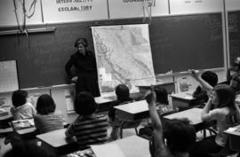 Iona Campagnolo standing beside a map of BC and talking to Haida Gwaii students