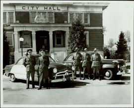Five British Columbia Police officers standing next to two police cars in front of Port Coquitlam...