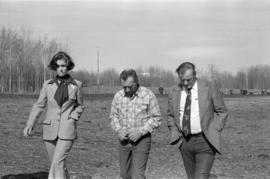 Iona Campagnolo, Minister Jack Horner, and unidentified other walking through a cow pasture in Sm...