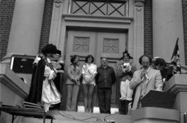 Iona Campagnolo, Miss Prince Rupert, and Mayor Peter Lester behind announcer at door of Prince Ru...
