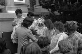 Iona Campagnolo shaking hands with a group of women dressed in chicken costumes in front of Princ...