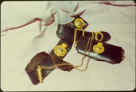 Closeup of Royal Irish Constabulary leather belt and case with attached gold badges and chain