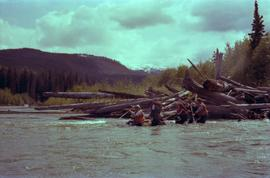 Iona Campagnolo and unidentified men paddling raft on Kitimat River during Delta King Days event