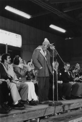 Man speaking into microphone onstage in an arena with Iona Campagnolo clapping beside him