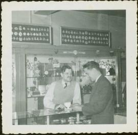 James Joseph Claxton and an unidentified man conversing the jewelry counter at at of Roderick Jew...