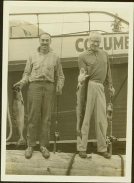 Two fishermen pose for a photo in front of the Columbia